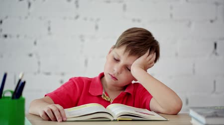 erudite : Schoolboy tired of reading the textbook Stock Footage