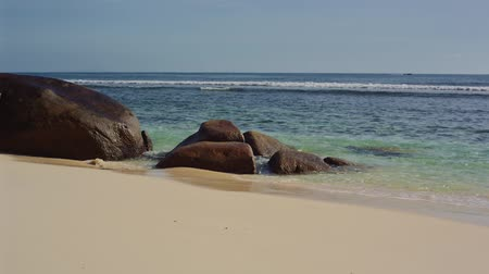 türkiz : The ocean washes large stones on the shore of Seychelles Stock mozgókép