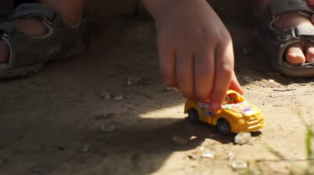 Five years old boy playing with yellow toy car on the ground.