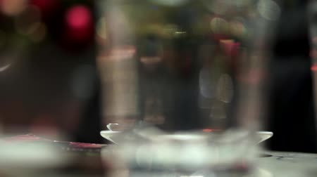 Womans hand taking a cup of coffee from the table and putting it back. Camera view through glass of water.