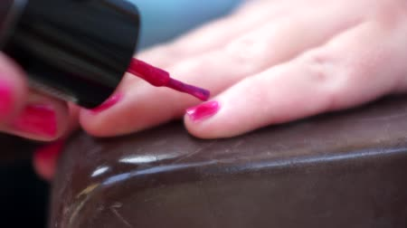 Woman painting her fingernails with pink nail polish.