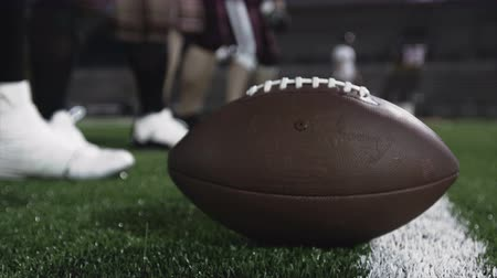 sportowiec : Close up of a football players hand snapping the ball to the quarterback