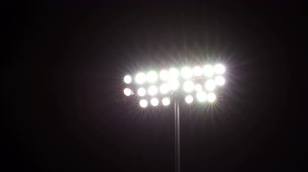 estádio : Isolated shot of stadium flood lights turning on a black sky background Stock Footage