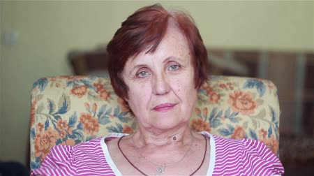 výraz : elderly woman sits and looks into the distance