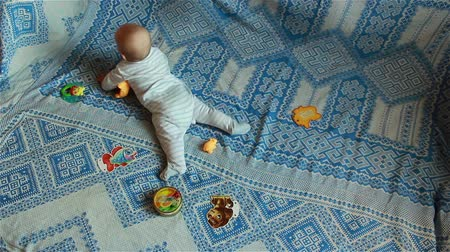 emzik : infant lying on the bed, playing with toys in timelapse