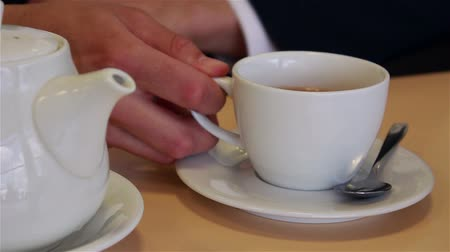 пробуждение : male hands close up pour tea into a cup and mixing spoon