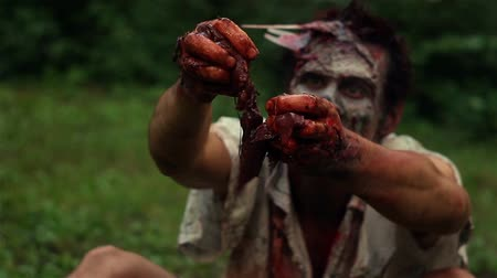 frightful : scary zombie sitting on green grass and tearing raw meat hand