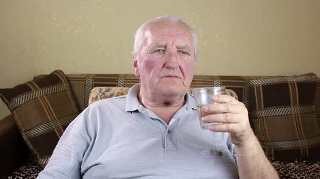 аперитив : Elderly man drinking water from a glass.