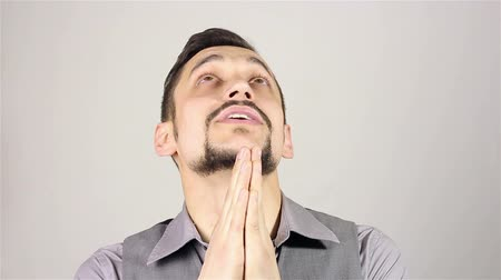 žádat : Young bearded man praying, asking God for help.