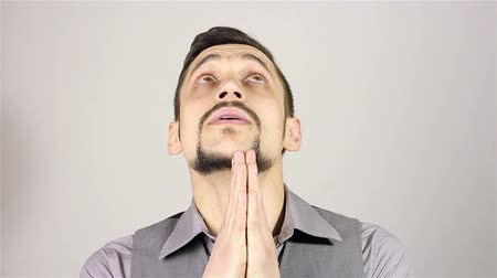угождать : Young bearded man praying, asking God for help.