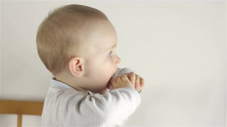 gevşemiş : Portrait of little baby girl . He holds his hands in his mouth, teeth grow Stok Video