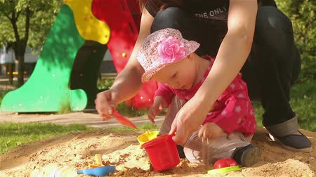 A little girl is playing with her mother in the sandbox.