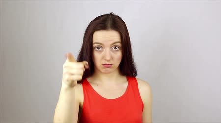 ведущий : Young beautiful woman pointing a finger at the camera. Gesture You