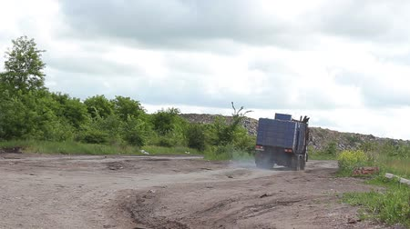 A garbage collector is driving through a city dump. Stock Footage