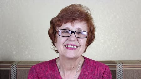 восхищенный : Beautiful elderly bespectacled woman smiling and looking at the camera Стоковые видеозаписи
