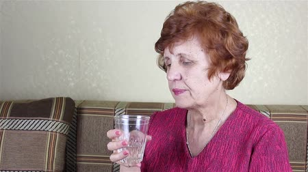 An elderly woman drinks water from a glass