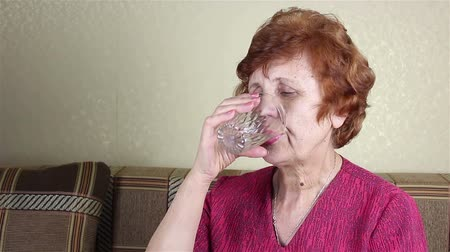 caneca : An elderly woman drinks water from a glass