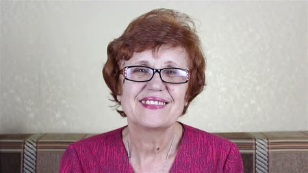 Beautiful elderly bespectacled woman smiling and looking at the camera Stock Footage