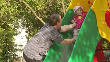 Happy father playing with baby girl on the playground