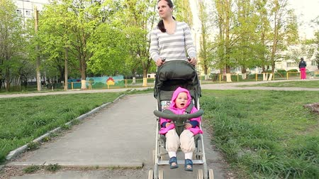wozek dzieciecy : Mom wears a baby girl sitting in a stroller. Walking along the path Wideo
