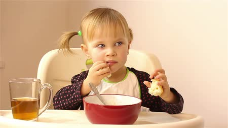 lžíce : A small two-year-old girl eats porridge.