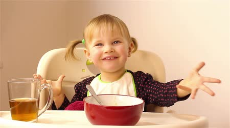 zabkása : A small two-year-old girl eats porridge.