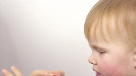daily : Skin care. Portrait of a beautiful little girl, mom putting moisturizing cream on her face.