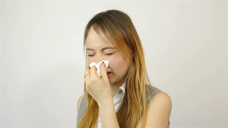 zsebkendő : Beautiful young woman sneezing into a handkerchief Stock mozgókép