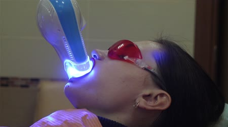 lézer : Young woman getting UV whitening at the dentists office by an ultra violet machine.