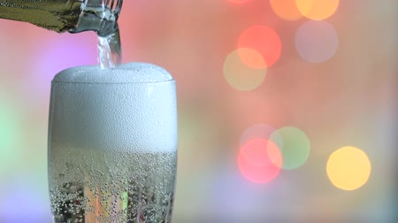 konfetti : Glass of champagne and a colorful defocused new year party background