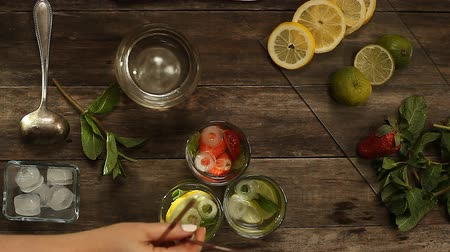 cytryna : preparation of three summer cocktails on a wooden table. view from above Wideo
