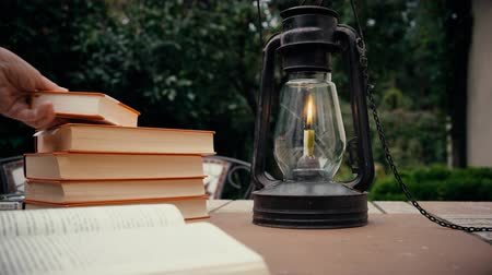 lampa naftowa : kerosene lamp and stapka old books on the table in the garden. hand puts the book on the table. autumn Wideo