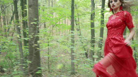 corrida : Steadicam shot of a woman in red lomg dress running away in forest