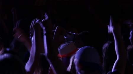 rock music : UKRAINE, VINNITSA - AUGUST 10, 2016: Audience with hands raised at a music festival and lights streaming down from above the stage Stock Footage