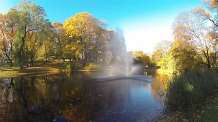 bástya : Timelapse of the Fountain and Rainbow in Riga Canal That Flows Through Bastion Park Autumn Background With Colored Leaves (Bastejkalns). Latvia Autumn