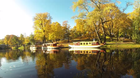 riga : Timelapse of Tourist Boats Autumn Park in the Center of Riga, Latvia Canal That Flows Through Bastion Park Autumn Background With Colored Leaves (Bastejkalns).. Famous Tourist Place in Baltic Region
