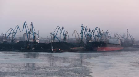 fosilní : Freight Shipping Containers and Gas Oil Tanks at the Docks. In Import Export and Business Logistic. Cargo Ship Docked at at the Port. Cargo Cranes by Winter Evening in the Port Riga, Latvia. Dostupné videozáznamy