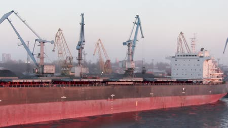 Латвия : Freight Shipping Containers and Gas Oil Tanks at the Docks. In Import Export and Business Logistic. Cargo Ship Docked at at the Port. Cargo Cranes by Winter Evening in the Port Riga, Latvia. Стоковые видеозаписи