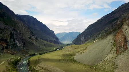 Altay mountain valley. Mountain river flowing between high snow-capped mountains. Kazakhstan East Asia and Russia. Dron footage.