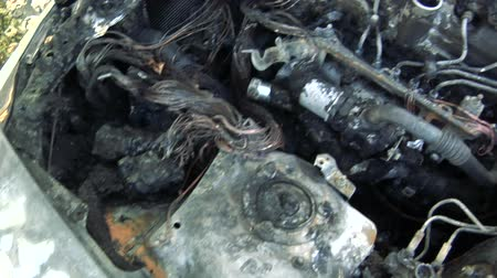 terrorisme : De auto na het vuur. Uitgebrande auto met een open kap. Engine Burned Out Car Wreck After a Fire. Vandalisme.