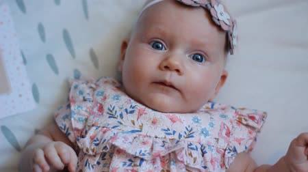 три человека : Close-up of a Three Months Old Baby Girl With Blue Eyes. Newborn Child, Little Adorable Peaceful and Attentive Girl Looking Surprised Smiling at the Camera. Family, New Life, Childhood Concept
