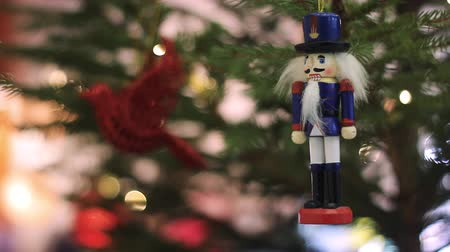 kardan adam : Nutcracker Soldier on a Christmas Tree With Blurred Background. Christmas Tree With Defocused Blurred Lights Bokeh. Christmas Nutcracker Figurine. Christmas Tree With Bokeh Background. Stok Video