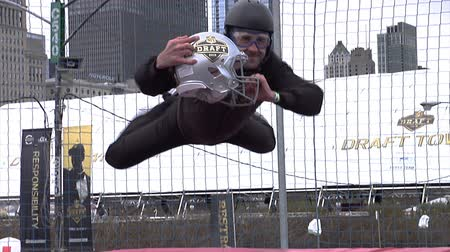 parachuting : Chicago - April 30, 2015 NFL Draft. Skydiving Simulator Wind Tunnel at the Draft Town.The Attraction Is Called the Sweetness Simulator NFL Fans Fly Against the Backdrop of the Chicago Skyline.