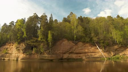 geological feature : Timelapse of the Velnala Cliffs. The Biggest Rock Outcrops in the Pikenes Bluff. These Cliffs and the Cave Are Located in the Valley of Gauja River Sigulda Latvia.