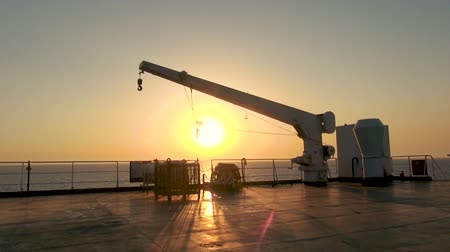 marine technology : Farry or Ship Crane at Sunset. Sea in the Background.