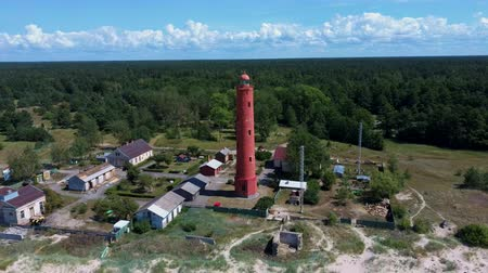 ориентация : Areal Dron Shot Akmenrags Lighthouse on the Latvian Coast of the Baltic Sea, Located to the South of the Resort Town of Pavilosta. Sunny Summer Day. The Current Tower Was Constructed in 1921 Стоковые видеозаписи