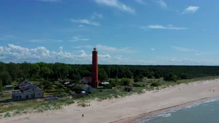 Areal Dron Shot Akmenrags Lighthouse on the Latvian Coast of the Baltic Sea, Located to the South of the Resort Town of Pavilosta. Sunny Summer Day. The Current Tower Was Constructed in 1921 Dostupné videozáznamy