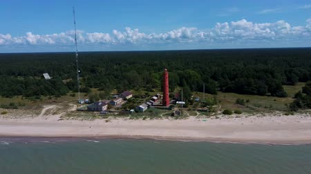 Латвия : Areal Dron Shot Akmenrags Lighthouse on the Latvian Coast of the Baltic Sea, Located to the South of the Resort Town of Pavilosta. Sunny Summer Day. The Current Tower Was Constructed in 1921 Стоковые видеозаписи