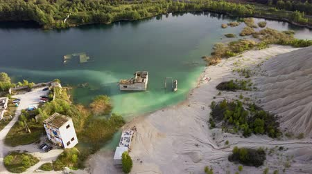 taş ocağı : Aerial landscape Sand Hills of Quarry With a Pond and Abandoned Prison in Rummu Estonia Europe. Flooded Houses of Former Prison. Mountain in the Abandoned Mines Sunken Ruins of Soviet Time Prison Stok Video