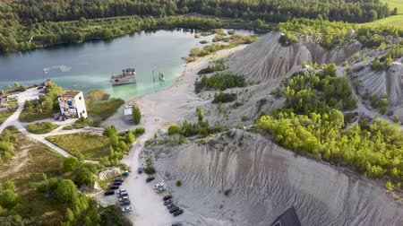 Észtország : Aerial landscape Sand Hills of Quarry With a Pond and Abandoned Prison in Rummu Estonia Europe. Flooded Houses of Former Prison. Mountain in the Abandoned Mines Sunken Ruins of Soviet Time Prison Stock mozgókép